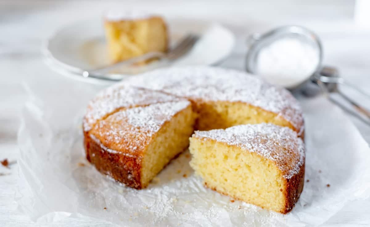 Pastel o bizcocho de vanilla servido sobre una superficie blanca.