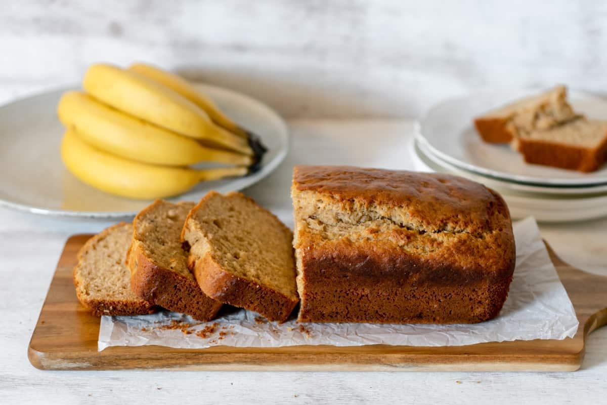 Banana bread casero partido en rebanados servido sobre una tabla de madera acompañando de bananos frescos.