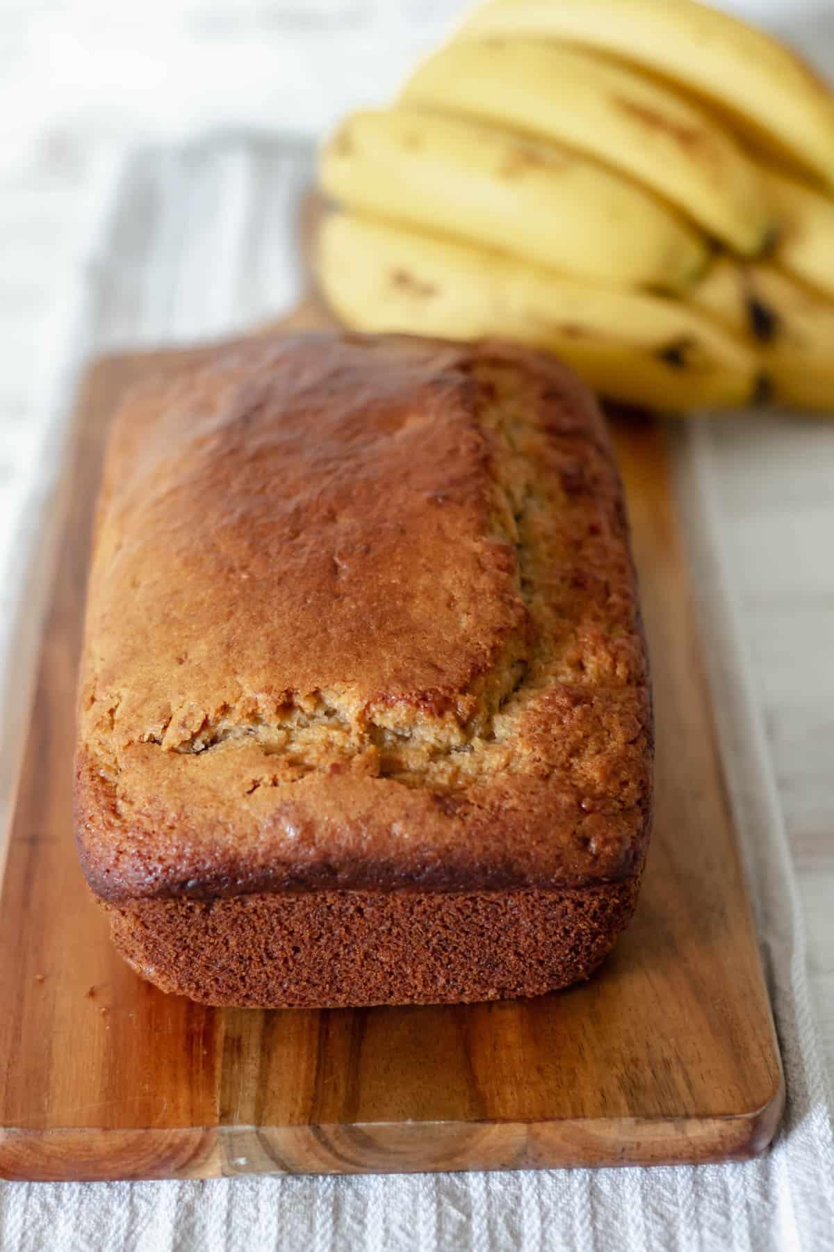 pan de plátano servido sobre una tabla de madera con bananos frescos en la parte de atrás.