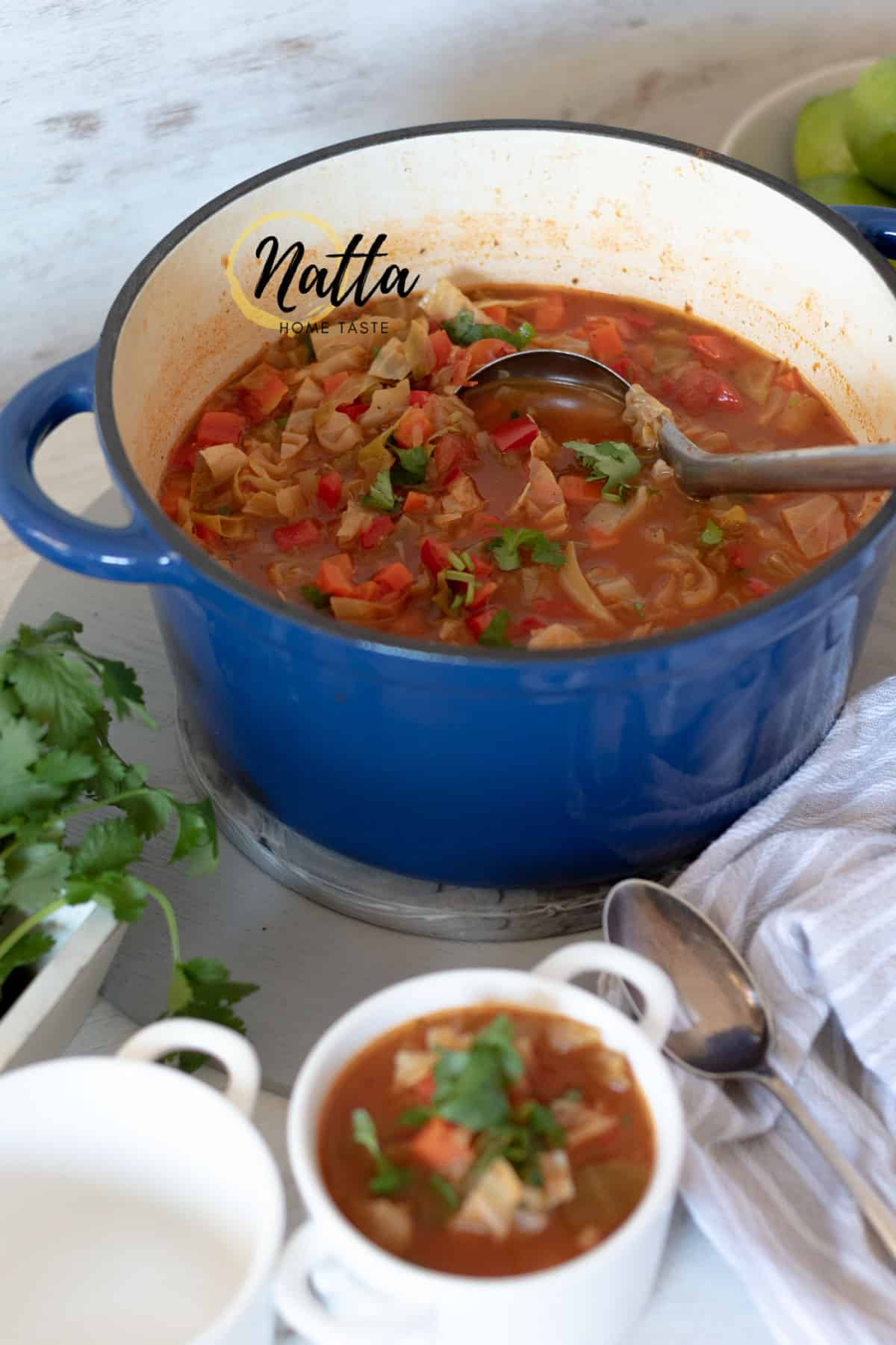 Sopa de repollo servida en una olla azul acompañada de recipientes blancos y cucharas
