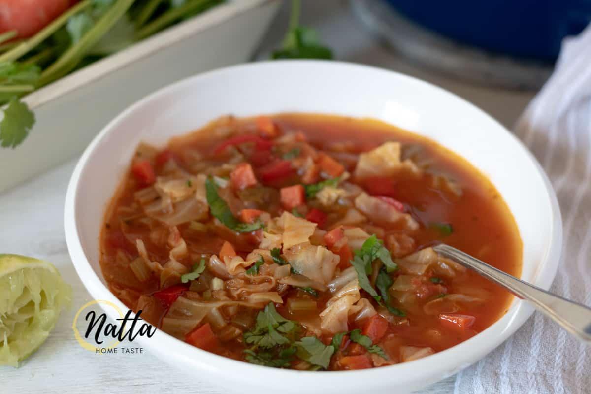Sopa de repollo servida en un plato blanco con una cuchara plateada