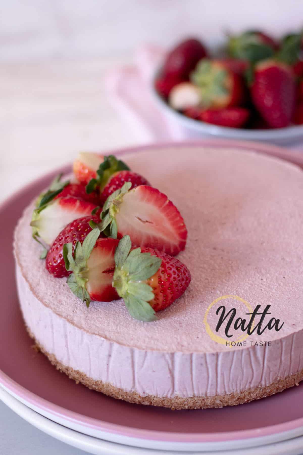 Cheesecake  vegano de fresa servido en un plato rosado.