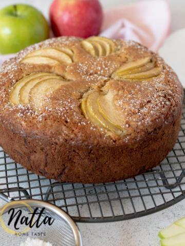 torta de manzana sobre una mesa blanca con 2 manzanas atrás